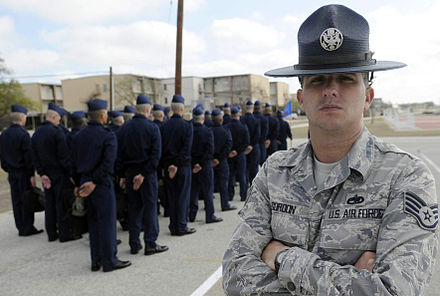 A Staff Sergeant Military Training Instructor (MTI) at Lackland in 2009. RH&T dormitories in background. Basic Military Training Instructor.jpg