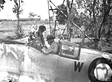 An old man wearing a hat and white shirt sitting in the cockpit of a silver aircraft. A younger man is leaning into the cockpit.