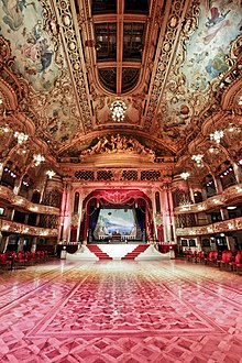 A large room with red floor and red and gold decoration to the walls. There is a stage at the back of the picture with seating areas to the sides.