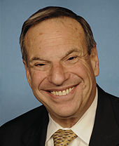 Waist high portrait of man in his sixties, smiling in a black suit