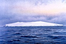 A low ice-covered island in blue choppy water, under a heavily clouded sky