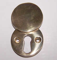 A Brass Escutcheon Plate. The Upper Disc Is Hinged, Allowing It To Swivel  Over The Open Keyhole, Or Aside To Allow The Keyhole To Be Used.