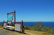 There are wooden information signs in the foreground, left and Lake Superior in the distance beyond the top of Brockway Mountain.