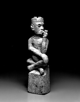 "Kingdom of Kongo - Kongo (Boma subgroup). Grave Marker (Tumba), 19th century. The Kongo place stone figures called tumba on the graves of powerful people. This chief is shown smoking a pipe with his head averted as if in a state of contemplation. His cap (mpu) with four leopard's teeth, the beaded necklace, and the bracelet (nlunga) identify the individual as a chief. The term tumba comes from the old Portuguese word for ""tomb""—this genre may have been inspired by grave monuments for European merchants and missionaries in Kongo cemeteries. Brooklyn Museum"