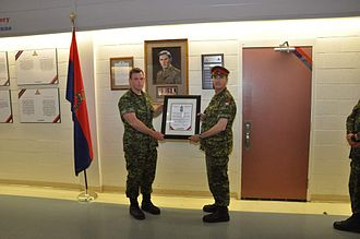 Norman Buchanan - A Student on the Forward Observation Officer Course is presented with the Norman Buchcanan Award through distinguishing himself as the top Candidate. A portrait of Norman Buchanan along with reproduction medals and history are displayed in the background.