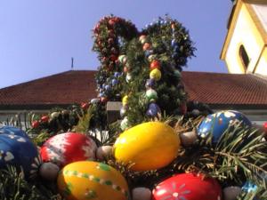 Burghaslach - Easter-decorated market fountain of Burghaslach, in the background St. Ägidius's Church