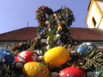 Burghaslach - Easter-decorated market fountain of Burghaslach, in the background St. Ägidius's Church