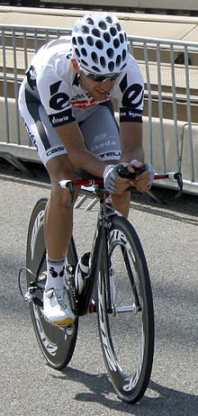 A road racing cyclist in a mostly white jersey with black trim riding a bicycle with a solid disc rear wheel.