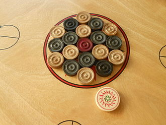 Carrom - Carrom men and one striker, arranged at the start of a game