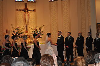 Wedding - A couple exchange vows on the church altar during a ceremony in a Catholic Church.