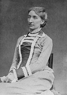 A photograph of a dark-haired white woman of about 40 sitting in an upright chair. She wears a long sleeved, collared dress with decorative material down the front and at the cuffs and neck.