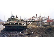 A heavily damaged tank which has lost its right-hand tracks sits next to a mine crater beside a road, with its barrel facing right and ruined houses in the background.