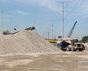 Environmental impact of concrete - Recycled crushed concrete being loaded into a semi-dump truck to be used as granular fill.