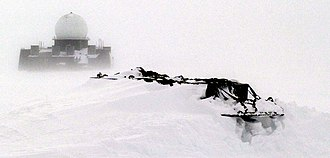 Distant Early Warning Line - A DEW station in western Greenland is visible in the distance beyond the snow-drifted equipment pallets in the foreground of this photograph.