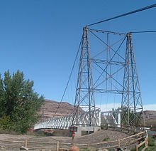 A view of a cable suspension bridge with one metal tower and a wooden deck. The second tower is partially obscured by a cottonwood tree.