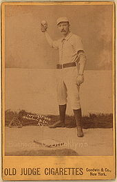 A baseball player is shown standing in his baseball uniform and gear used for a catcher.