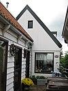 foto van Houten huisje met lage achteraanbouw, tegen nr. 92 aan gebouwd. Uiterlijke vorm 19e-eeuws. Punttoppen