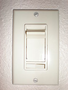 Vertical rectangular plastic cover plate with vertical slider and a smaller horizontal rocker switch below. Two exposed slotted screw heads hold the cover plate to the wall box.