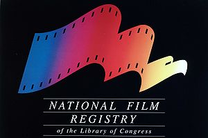 "The image includes a logo on a black background. The logo looks like a film reel and changes from left-to-right to an eagle. The logo is multi-colored and below it is the phrase ""National Film Registry of the Library of Congress""."