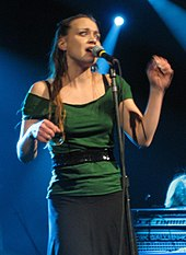 A woman wearing a green shirt, black belt and a dark gray skirt, standing behind a microphone on a stage.