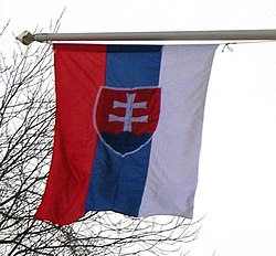 When flown vertically the coat of arms is rotated. Note: If hoisted properly the white field should be towards the finial; therefore in this example the flag is incorrectly hoisted.
