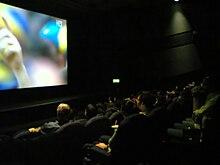 Photo d'une salle de cinéma encore éclairée en pleine projection d'un match de football en haute définition.