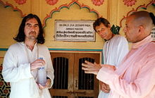 Three men in their early fifties, one on the left, wearing a white robe and holding a bottle of water with both hands, and two on the right, one in a white robe and one in a pink robe. On the wall behind them is something written in Sanskrit, both in Roman characters and in Sanskrit characters.