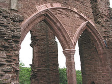 Part of a castle, with a huge semi-circular arch containing two smaller Norman arches dominating the picture. Through the arches, a ruined pillar can just be made out.