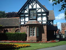 A two-storey house, the lower storey being in sandstone and the upper timber framed and gabled. To the right of the house are the entry gates to the park and in front of it are formal flower beds.