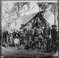 Group of people, one with a banjo, outside a tent, Australia, ca. 1900 (16216443634).jpg