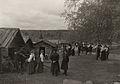 Högtidsklädda människor samlade utanför kyrkstallarna vid Rättviks kyrka i Dalarna - Nordiska Museet - NMA.0060672.jpg