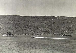 Raid on Souda Bay - York and Pericles both crippled and beached. A Short Sunderland flying boat is landing between them