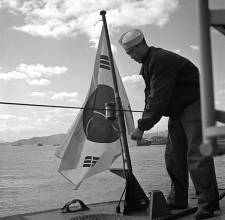 A ROKN sailor places a S. Korean naval ensign on a torpedo boat, after its transfer by the U.S. in the midst of the Korean War. HN-SN-98-07198.JPEG