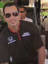 Man in his mid thirties smiling at the camera. He is wearing a black T-shirt and sunglasses.
