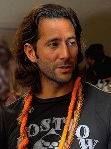 A bearded, long-haired man in a black shirt, with orange necklaces around his neck.
