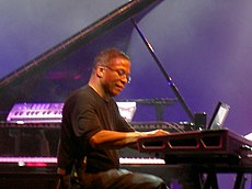 A Black man wearing a black t-shirt plays keyboard.