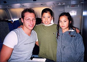 "A young man is at left wearing a tight grey t-shirt with white sleeves, with ""French Connection"" across his chest. He has short hair and is wearing elliptical glasses. In the centre is a boy with very short black hair in a green T-shirt, and to the right is a young girl with pigtails wearing a blue coat. They are posing on an aeroplane."