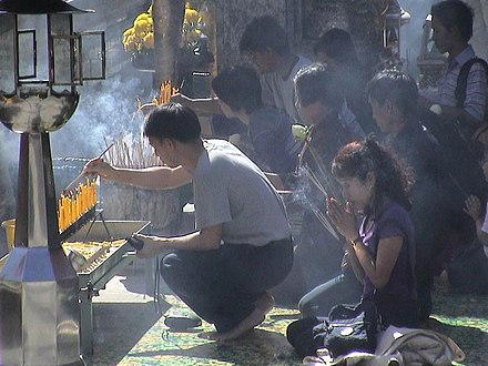 Buddhists praying with incense at Wat Phra Kaew, Thailand Incense-LE.jpg