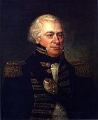 A man with white, receding hair in a high collared military coat with gold accents over a white shirt