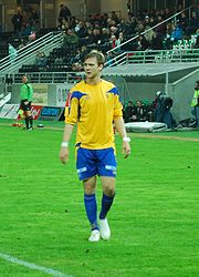 A brown-haired Caucasian American is standing in the center of a grass field, his body facing the camera and his head turned away, and wearing the blue and yellow soccer uniform of his former Norwegian club, Alta.