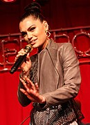 A Caucasin female with her hair in a bun, large gold hoop earrings, and a chocolate-colored animal skin jacket sings into a microphone with her hand flat simulating a pushing motion. She stands in front of a red background and only appears from the waist up.