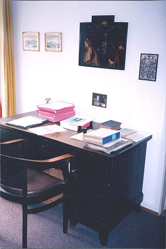 Karl Barth - A desk in Karl Barth's old office with a painting of Matthias Grünewald's crucifixion scene