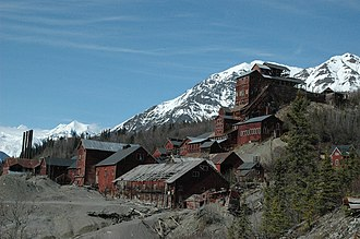 Kennecott, Alaska - The 14-storey Kennicott Concentration Mill (to the right), the mines are 5 miles up in the mountains to the east/northeast. Also pictured - foreground (left to right): power plant, machine shop, flotation plant, ammonia leaching plant (world's first); in the trees to the right - general manager's office (log cabin portion was first building built in Kennicott)