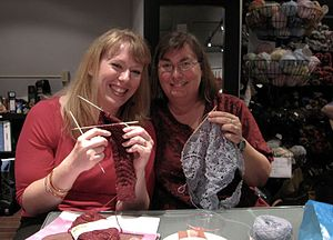 Two women knitters with blogs, holding up thei...