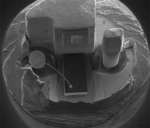 SEM (Scanning Electron Microscope) image of a commercial laser diode with its case and window cut away. The anode connection on the right has been accidentally broken by the case cut process. Laser diode with case cut away.jpg