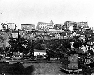 Pike Place Market - Looking east from the Elliott Bay waterfront between Stewart and Virginia Streets. The dirt track rising at left is part of Stewart Street. The first Washington Hotel (1891–1906, center, background) sits atop the small, steep Denny Hill, regraded in 1906–1907. This is taken from somewhere near Railroad Avenue, the present-day Alaskan Way.
