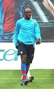 A dark-skinned man wearing a teal shirt, black pants, and blue, deep red socks.