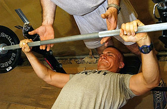 Spotting (weight training) - A man (lying down) performs a bench press with a spotter.