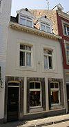 foto van Huis met in de gepleisterde lijstgevel een segmentboogingang en -vensters in Naamse steen.