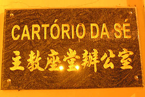 "Culture of Macau - A sign in both Chinese and Portuguese in Macau - ""主教座堂辦公室"" (in Chinese) and ""Cartório da Sé"" (in Portuguese), which means ""Office of the Cathedral."""